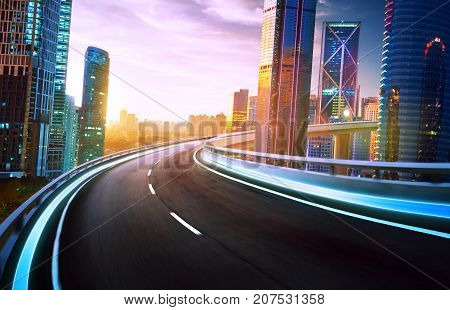 Highway overpass motion blur with city skyline and urban skyscrapers sunset and twilight scene.
