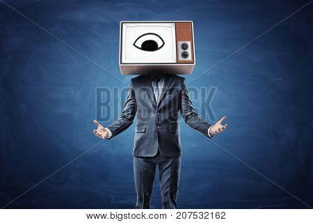 A businessman with both arms in front of him palms up and a head replaces by a TV box with an eye on a screen. Corporate control. Supervision at work.