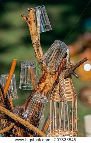 Ornamental support of branches used for glasses and bottle covered with twigs and wicker.