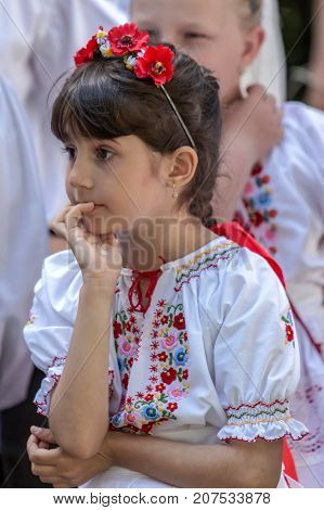 ROMANIA TIMISOARA - JUNE 11 2017: Nice attitude of one young Romanian girl in traditional folk costume present at traditional event Festival of ethnics