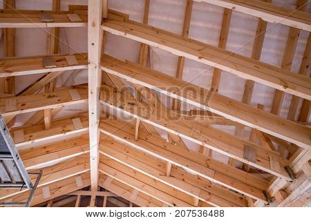 Construction of frame wooden house. Interior view of a wooden roof structure