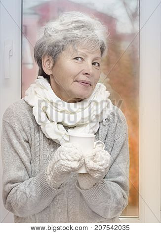 Gray haired woman in white knitted gauntlets drink beverage and smiling on autumn window background. Elderly woman with mug. Soft filter. Autumn toning effect