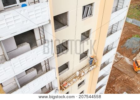 The Painter Works On The Lift Of A New Building