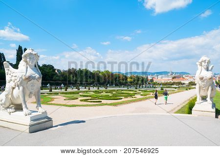 Vienna Austria - August 7 2016: The garden with Sphinx statues of the Belvadere Palace with the lower palace in the background
