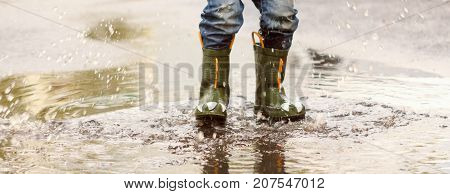 child with rain boots jumps into a puddle with leaf autumn concept
