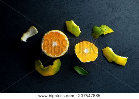 Peeled yellow mandarin and peel on a gray table horizontal