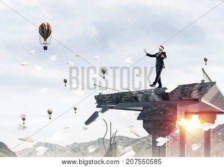 Businessman walking blindfolded on concrete bridge with huge gap as symbol of hidden threats and risks. Flying balloons and nature view on background. 3D rendering.