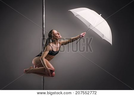 Pole Dance Comcept. Young Woman With Umbrella Exercising Pole Dance On Gray Background