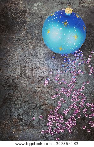 Christmas decorations - blue ball and sequins over dark background, focus on sequins, retro toned