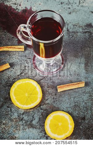 Spilled mulled wine and cinnamon over dark background, retro toned