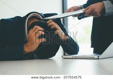 Angry boss giving a document to a sad employee sitting in a desk at office