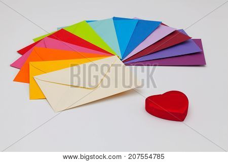 Different colored envelopes and red heart on the table