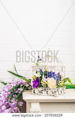 White vintage decorative bird cage with beautiful purple flowers