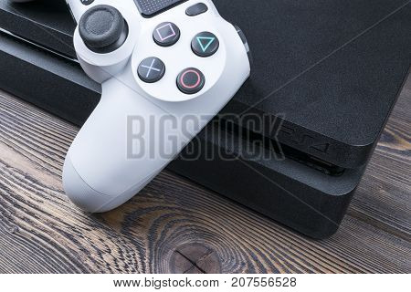Sankt-Petersburg Russia September 24 2017: Sony PlayStation 4 Slim 1Tb revision and dualshock game controller. Game console with a joystick. Home video game console on wooden table