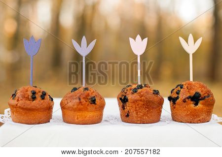 Four baked cake with topper in the shape of flowers