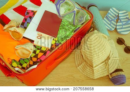 Opened traveler case Suitcase on table. Red Suitcase with different things prepared for travel - Retro color
