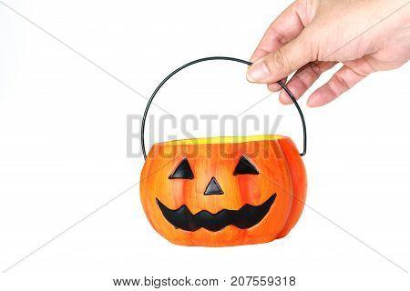 Halloween concept : hand holding ceramic Halloween Pumpkin bucket isolated on white background