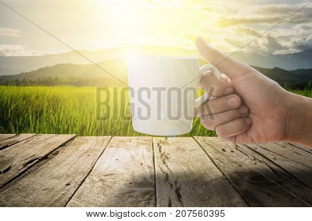 woman hand holding a white coffee cup with green meadow and mountain in the morning with the sunbeam on the old wooden terrace.