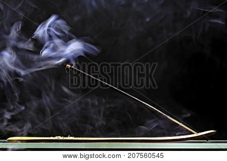 Incense stick smolders and emits intensive smoke on black background