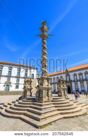 Porto, Portugal - August 11, 2017: Porto Pillory or Pelourinho a manueline column, symbol of the power of justice in historic center of Oporto. Episcopal Palace on background. Sunny day, blue sky.