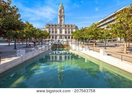 Porto, Portugal - August 11, 2017: Porto City Hall or Camara Municipal do Porto water reflection in Avenida dos Aliados, Liberty square, Oporto in Portugal. Sunny day in the blue sky.