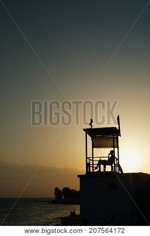 Black silhouette of observation tower and person in it on coastline in sunset time.