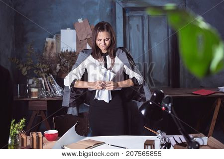 Young business woman scribbling documents at camera. Disappointed and annoyed by unsuccessful project.