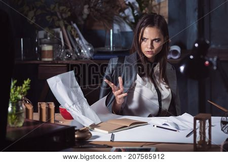 Young business woman throwing documents at camera. Disappointed and annoyed by unsuccessful project.