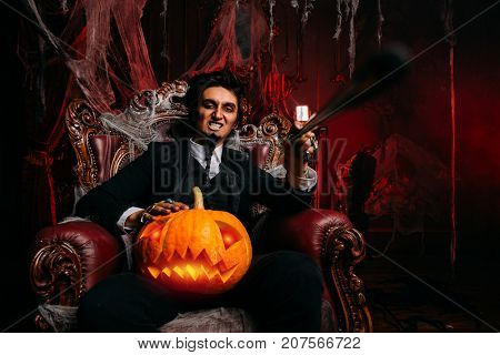 Halloween. Mysterious and frightening man aristocrat vampire in an old abandoned castle sits in an armchair with a pumpkin-lantern.