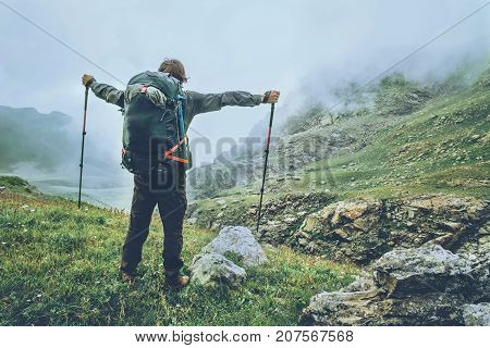 Happy Man backpacker hiking in foggy mountains raised hands Travel Lifestyle adventure wanderlust concept summer vacations active outdoor