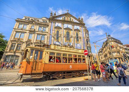 Porto, Portugal - August 11, 2017: Porto Tram City Tour and people in front of Azulejo facade of Saint Anthony's Church Congregados, Almeida Garrett square, Porto historic center