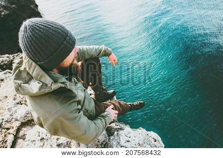 Man traveler sitting on cliff alone thinking above deep sea Travel Lifestyle concept vacations outdoor solitude emotions aerial view