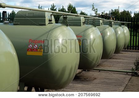 Large group of propane gas storage tanks in security compound.