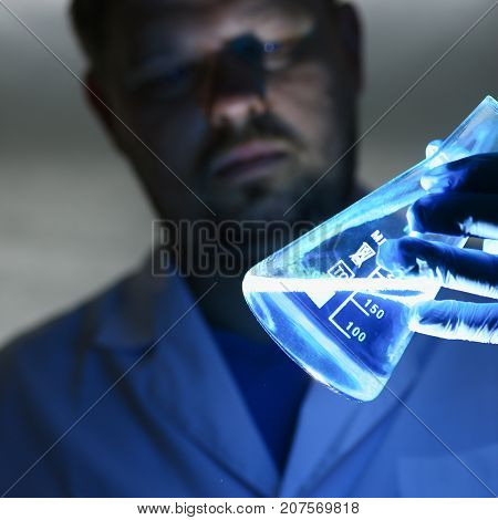 A chemist holds in his hand a flask with a blue liquid that the virus received a poison vaccine in the laboratory with the help of synthesis dangerous for the zodiac worked diligently