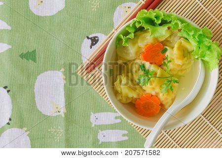 Homemade minced pork and shrimp wonton soup or dumpling soup in white bowl on wood table in top view flat lay with copy space. Delicious dumpling soup for breakfast or lunch or dinner. Wonton soup or dumpling soup is popular Chinese food.