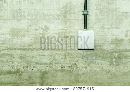 White electrical power outlet with cover cap and black cable attached on grunge concrete wall