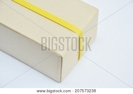 brown hard paper box wrapped by yellow plastic band on white background