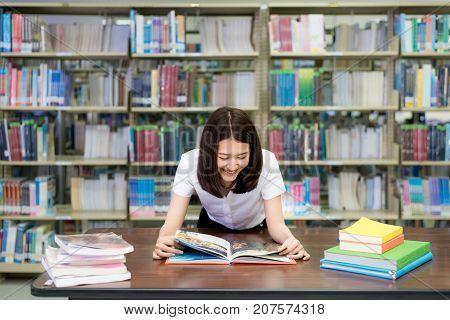 Cheerful female Asian student reading book during break between lesson near bookshelves in modern interior library of university.
