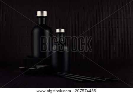 Dark black minimalist interior. Blank black cosmetics bottles on dark wood board with copy space. Noir elegant home decor for advertising designers branding identity cover.