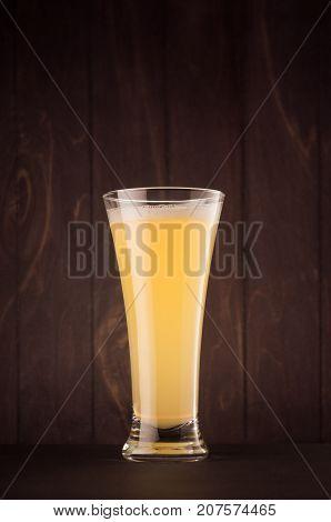 Pilsner beer glass with muddy weizen on dark wood board vertical. Template for advertising design branding identity restaurant menu cover.