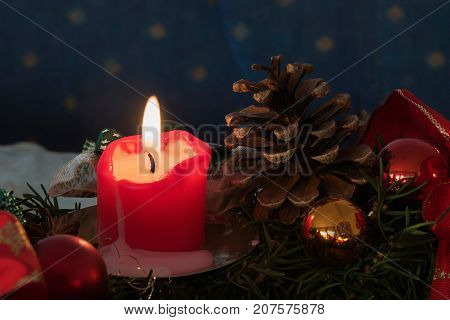 Lighted Candle In An Advent Decoration With Cones And Baubles