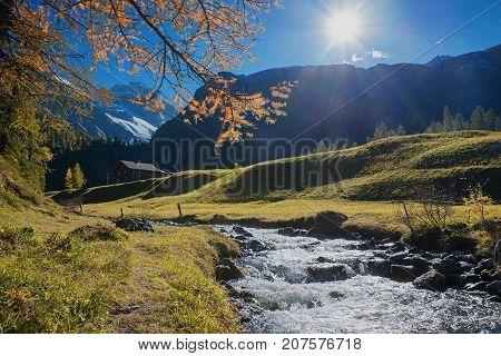 Idyllic Path Beside Little Brook In Autumnal Swiss Landscape