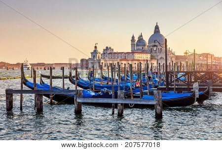 Gondolas on Grand Canal in Venice Italy sunset view Cathedral of Santa Maria della Salute picturesque skyline landscape.