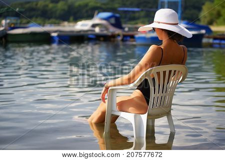 Slim woman in swimsuite with sunhat on head sitting on white chair in water