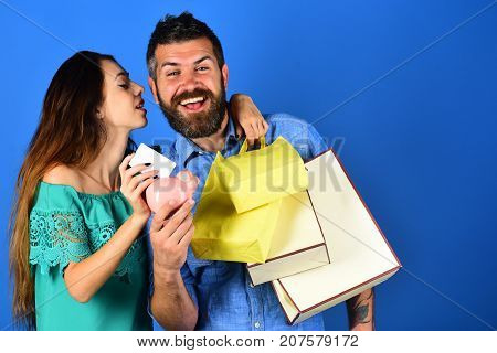 Man With Beard Holds Credit Card And Piggy Bank.