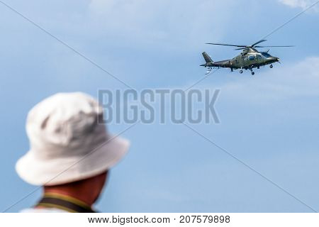 SLiAC SLOVAKIA - AUGUST 27: Man watching on helicopter Augusta A-109 and flares at airshow SIAF 2017 on August 27 2017 in Sliac