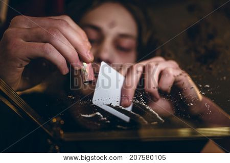 Close-up low-angle view of the hands of an addicted young man snorting powdered cocaine with a rolled banknote at home
