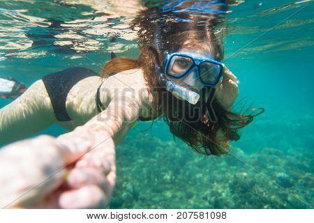 Snorkelling woman in yellow bikini makes tempting gesture in ocean