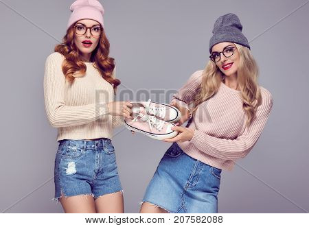 Young Woman Surprised Having Fun. Fashion. Shopping Sales Discount concept. Pretty Sisters Best Friends Twins in Stylish fashion Autumn Winter Outfit. Playful Hipster Model Girl in Cozy Jumper, Glasses