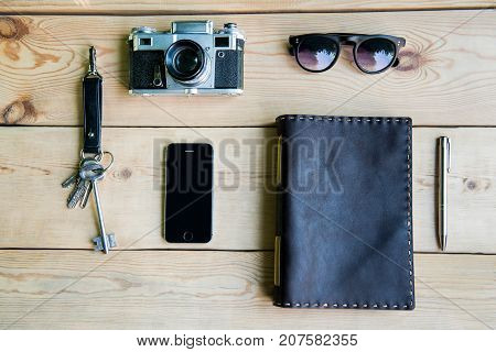 Personal everyday accessories of urban people: camera, smartphone, keys, notebook, sunglasses; pen. Background.